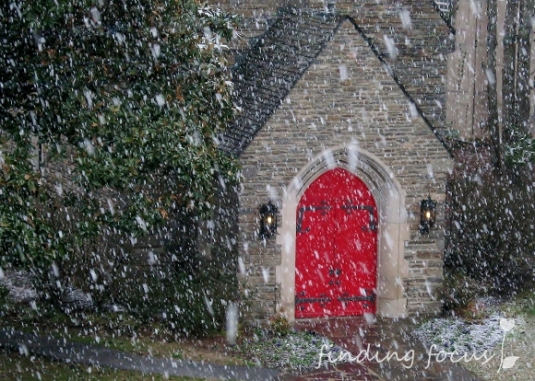 stone church red doors hidden in snowfall