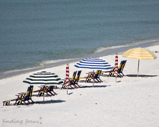 colorful beach umbrellas white sand blue water